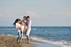 Den lyckliga unga familjen har gyckel på strand Arkivbild