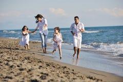 Den lyckliga unga familjen har gyckel på strand fotografering för bildbyråer