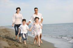 Den lyckliga unga familjen har gyckel på strand Arkivfoton