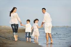 Den lyckliga unga familjen har gyckel på strand på solnedgången Royaltyfri Fotografi