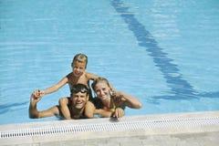 Den lyckliga unga familjen har gyckel på simbassäng Royaltyfri Foto