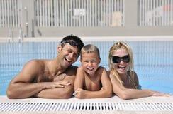 Den lyckliga unga familjen har gyckel på simbassäng Royaltyfri Fotografi