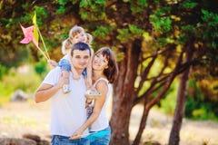Den lyckliga unga familjen med barnet som utomhus vilar i sommar, parkerar Arkivfoton