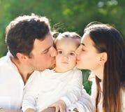 Den lyckliga unga familjen med behandla som ett barn flickan Arkivfoto