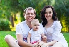 Den lyckliga unga familjen med behandla som ett barn flickan Arkivbilder