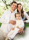 Den lyckliga unga familjen med behandla som ett barn flickan utomhus Arkivfoto