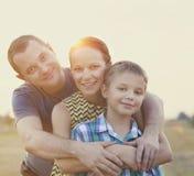 Den lyckliga unga familjen med behandla som ett barn flickan utomhus Arkivbild