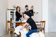 Den lyckliga unga familjen och den lilla sonen poserar på vagga häst hemma royaltyfri bild