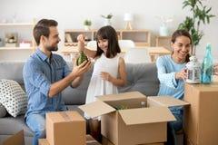 Den lyckliga unga familjen packar upp askar som flyttar sig till det nya hemmet royaltyfria bilder