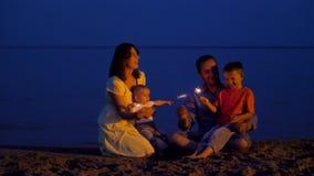 Den lyckliga unga familjen som firar på stranden på skymning, lurar och uppfostrar sjungande och hållande tomteblossfyrverkerier arkivfilmer