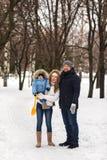 Den lyckliga unga familjen som går i en vinter, parkerar Royaltyfri Foto