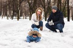 Den lyckliga unga familjen som går i en vinter, parkerar Arkivbild