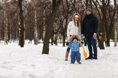 Den lyckliga unga familjen som går i en vinter, parkerar Arkivbilder