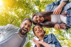 Den lyckliga unga familjen som tillsammans står och ler på kameran parkerar in Royaltyfri Foto