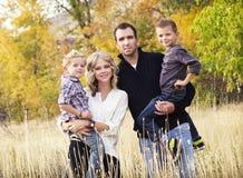Den lyckliga unga familjståenden med nedgången färgar Arkivfoto