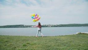 Den lyckliga unga flickan går med färgglade ballonger på kusten av sjön 4K arkivfilmer