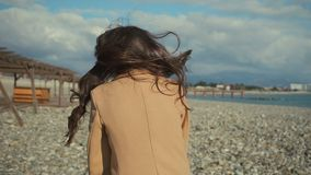 Den lyckliga unga flickan som tycker om, går på stranden arkivfilmer