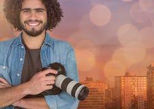 den lyckliga unga fotografen räcker vikt och kameran förestående framme av staden Överlappning med blått och Arkivfoton