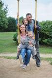 Den lyckliga unga gladlynta familjen av fyra på lekplats` s svänger Arkivbild