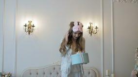 Den lyckliga unga härliga flickan i pyjamas packar upp julgåvan på sängen Lynne för ` s för nytt år stock video