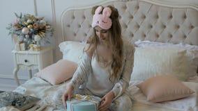 Den lyckliga unga härliga flickan i pyjamas packar upp julgåvan på sängen Lynne för ` s för nytt år lager videofilmer