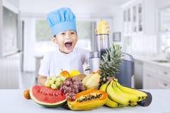 Den lyckliga pojken blandar sund fruktfruktsaft hemma Arkivbilder