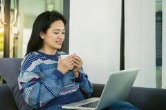 Den lyckliga unga kvinnan är avslappnande på den bekväma soffan och användabärbara datorn hemma royaltyfria foton