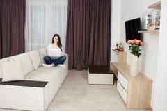 Den lyckliga unga kvinnan är avslappnande på den bekväma soffan och användabärbara datorn hemma arkivfoton