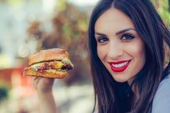 Den lyckliga unga kvinnan äter den smakliga snabbmathamburgaren Royaltyfri Fotografi