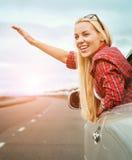 Den lyckliga unga kvinnan gör en stor gest från bilfönstret arkivfoto