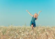 Den lyckliga unga kvinnan hoppar i fältet av kamomillar, Fotografering för Bildbyråer