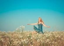 Den lyckliga unga kvinnan hoppar i fältet av kamomillar Arkivfoto