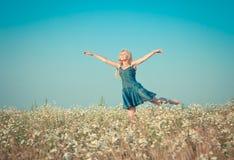 Den lyckliga unga kvinnan hoppar i fältet av kamomillar Fotografering för Bildbyråer