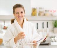 Den lyckliga unga kvinnan i badrock med exponeringsglas av mjölkar Fotografering för Bildbyråer