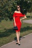 Den lyckliga lyckliga unga kvinnan i en stad parkerar köp Skönhet begreppet av mode Arkivfoto