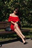 Den lyckliga lyckliga unga kvinnan i en stad parkerar på en bänk köp Skönhet begreppet av mode Royaltyfria Bilder