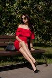 Den lyckliga lyckliga unga kvinnan i en stad parkerar på en bänk köp Skönhet begreppet av mode Arkivfoton