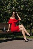 Den lyckliga lyckliga unga kvinnan i en stad parkerar på en bänk köp Skönhet begreppet av mode Royaltyfri Fotografi