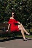 Den lyckliga lyckliga unga kvinnan i en stad parkerar på en bänk köp Skönhet begreppet av mode Royaltyfri Bild