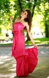 Den lyckliga unga kvinnan i lång klänning i en sommar parkerar Arkivbilder