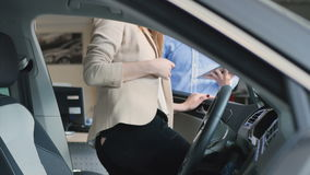 Den lyckliga unga kvinnan kontrollerar inre för bil` s och visar en representant för tumme upp till arkivfilmer