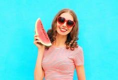 den lyckliga unga kvinnan ler och har gyckel med skivan av vattenmelon Royaltyfri Foto