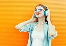 Den lyckliga unga kvinnan lyssnar och tycker om musik i hörlurar Arkivbild