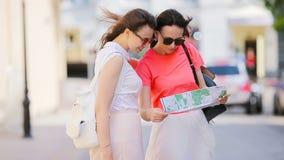 Den lyckliga unga kvinnan med översikten som promenerar stadsgatan i Europa, frågar hjälp en annan caucasian flicka