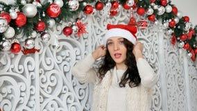 Den lyckliga unga kvinnan med det charmiga leendet som bär den Santa Claus hatten, ler, medan posera i studio på dekorerad jul arkivfilmer