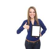 Den lyckliga unga kvinnan med digital minnestavlavisning tummar upp Fotografering för Bildbyråer