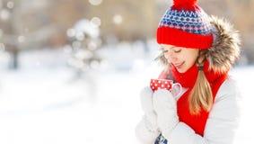 Den lyckliga unga kvinnan med en kopp av varmt te i vinter går Royaltyfria Foton