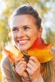 Den lyckliga unga kvinnan med höst spricker ut utomhus Arkivfoton