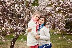 Den lyckliga unga kvinnan med hennes litet behandla som ett barn flickan Moder som går med dottern på en vårdag Tycka om för förä royaltyfria foton