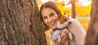 Den lyckliga unga kvinnan med hunden i höst parkerar utomhus Royaltyfria Bilder